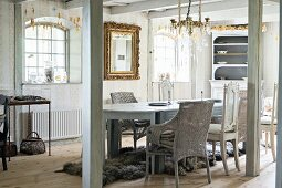 Vintage-style dining area with pastel chairs in rustic interior with heavy wooden beams