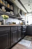 Kitchen counter with dark base and wall units in country-house kitchen