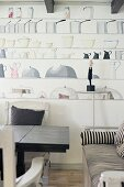 Dining table and couch with striped cover in front of wall with kitchen-themed mural