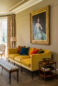 Yellow couch with colourful velvet scatter cushions and patterned footstool below antique, gilt-framed portait