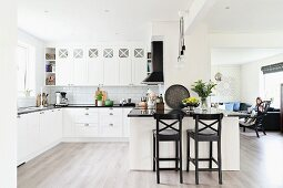 Open-plan white kitchen with black bar stools at counter and woman in lounge area in background to one side
