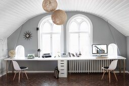 Attic room with arched ceiling and white wood panelling; long desk for two and classic chairs below arched windows