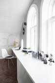 White desk against gable wall with arched windows