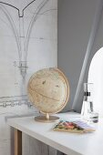 Vintage globe on desk and architectural drawing on wall