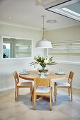 Round wooden table and chairs below pendant lamp with white lampshade in dining room