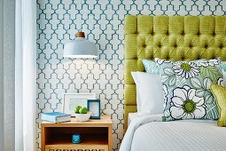 Wooden bedside cabinet below pendant lamp next to bed with yellow headboard against retro wallpaper