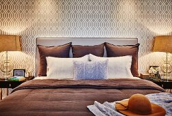 Pillows and cushions on double bed with upholstered headboard against wallpaper with beige retro pattern