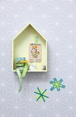 Easter arrangement in pastel shades; small wooden house on wall with rabbit ornament, quail's egg and ribbons