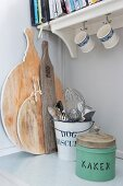 Vintage tin, metal bucket of kitchen utensils and wooden chopping boards on kitchen base unit below bracket shelf