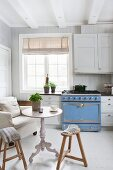White, Scandinavian country-house kitchen with pale blue gas cooker, armchair, table and wooden stools in vintage ambiance