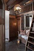 Lantern-style lamp in foyer of log cabin with cloakroom bench below mirror to one side