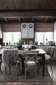 Rustic wooden chairs, some with animal-skin blankets, around dining table in rustic dining room of wooden house