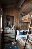 Bunk-beds in narrow children's bedroom in wooden house with vintage steamer trunk to one side