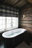 Free-standing bathtub below window with tartan roller blind in bathroom of wooden house
