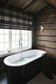 Free-standing bathtub below window with tartan roller blind in bathroom of wooden house