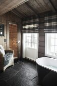 Bathroom with black slate floor, lattice windows, tartan roller blinds and view into sauna in background