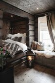 Lit candle in floor lantern next to cubby bed with fur blanket and window seat in wooden house