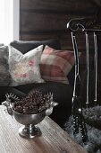 Silver bowl of pine cones on wooden table in front of sofa with scatter cushions