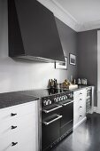 Elegant kitchen counter with extractor hood on grey wall