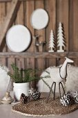 Festive table arrangement; animal figurines and fir cones on woven place mat and white ceramic vase of fir branches