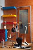 Putzutensilien und Retro Drahtgittersessel vor Holzdekor-Wand mit farbigen Borden