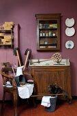 Alter Waschtisch, Wandschränkchen und antiker Armlehnstuhl mit Putzutensilien vor violetter Wand