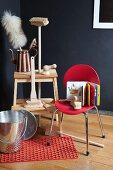 Putzbürsten mit Holzgriffen und Staubwedel auf Tritthocker; davor Metalleimer auf Rutschmatte und Stuhl mit Kinderbuch