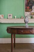 Various ornaments on wall-mounted shelf behind antique, oval exotic-wood table