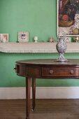 Verschiedene Dekoobjekte auf Wandablage davor antiker ovaler Edelholztisch