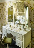 White dressing table with triple vanity mirror against wall with romantic, floral wallpaper