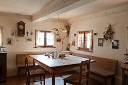 Restored farmhouse parlour with corner bench and rustic wooden table