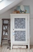 Shabby-chic cupboard with lace fabric in panelled door