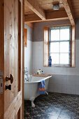View of vintage bathtub and patterned floor tiles in rustic bathroom seen through open door
