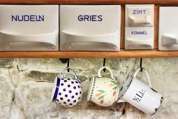 Labelled china scoops and vintage cups hung from hooks against stone wall