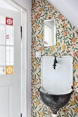 Vintage sink on wallpapered wall