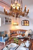 Vintage-style chandelier above set coffee table on vintage, Rococo-style lounge furniture