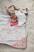 Pale grey picnic blanket with crocheted trim and seagull motif on sand