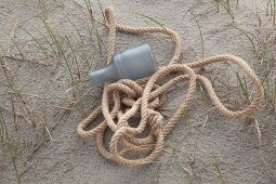 Rope and plastic bottle on sandy floor