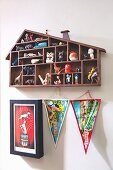 House-shaped display case above pennants and picture on wall
