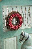 Kranz aus Baumrindenstücke und roten Äpfeln an verwitterte Holztür aufgehängt