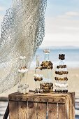 Glass bottles decorated with seashells on wooden crate on beach