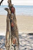 Flotsam on sandy beach: ropes and fishing nets