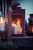 Laterne mit mehreren brennenden Kerzen auf Dachterrasse im Abendlicht