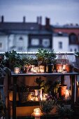 Potting bench atmospherically decorated with plants and candle lanterns on roof terrace at twilight