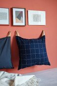 Hand-sewn cushions hung on pink wall from leather straps
