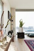 Branches in glass vase on rustic wooden bench, house plant in white planter on lattice table and glass wall with view of harbour entrance