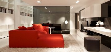 Red sofa combination and delicate side table on white flokati rug in open-plan lounge with smoked glass partition in background