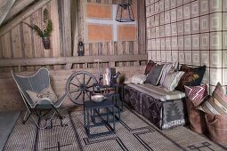 Butterfly armchair, metal side tables and comfortable bench with cushions against wall covered in vintage-look wallpaper