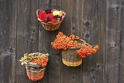 Baskets filled with berries and flowers hung on wooden wall