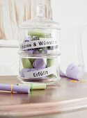 A glass jar filled with wishes written on coloured piece of paper